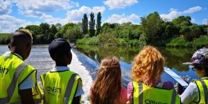 Students counting twaite shad on the bank of the river at Tewkesbury