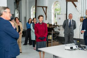 HRH The Princess Royal standing inside Diglis Workshop, smiling at a presentation being shown out of shot